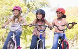 Tres amigos de la chica joven en la sonrisa de las bicicletas Imagenes de archivo