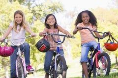 Tres amigos de la chica joven en la sonrisa de las bicicletas Imágenes de archivo libres de regalías