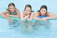 Tres amigos de la chica joven en piscina Imagen de archivo libre de regalías