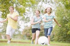 Tres amigos de la chica joven que juegan a fútbol Fotografía de archivo