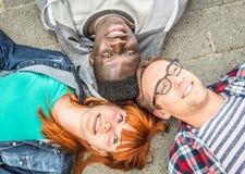 Tres amigos de la raza mixta que mienten en la tierra Fotografía de archivo