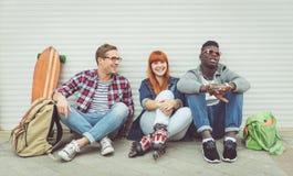 Tres amigos de la raza mixta que sientan y que se divierten Fotos de archivo