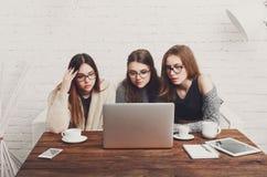 Tres amigos de las mujeres jovenes con el ordenador portátil Fotografía de archivo libre de regalías