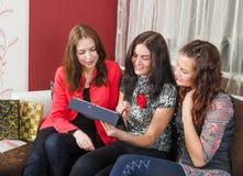 Tres amigos de las mujeres jovenes que charlan en casa y que usan el ordenador portátil a l Imagen de archivo