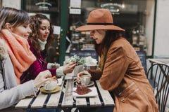 Tres amigos de las mujeres que comen café en una terraza en Oporto, Portugal Tener una conversación de la diversión Forma de vida fotografía de archivo libre de regalías