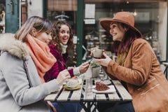Tres amigos de las mujeres que comen café en una terraza en Oporto, Portugal Tener una conversación de la diversión Forma de vida fotos de archivo libres de regalías