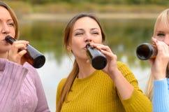 Tres amigos de las mujeres que gozan de una cerveza junta Foto de archivo libre de regalías