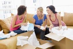 Tres amigos de muchacha que desempaquetan los rectángulos en nuevo hogar Imagen de archivo libre de regalías