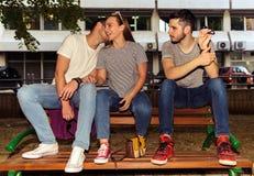 Tres amigos despreocupados que se sientan en el banco el día de verano Foto de archivo libre de regalías