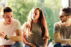 Tres amigos despreocupados que se sientan en el banco el día de verano Imagen de archivo