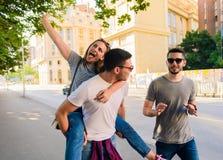 Tres amigos despreocupados que toman la 'promenade' en la ciudad Foto de archivo