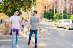 Tres amigos despreocupados que toman la 'promenade' en la ciudad Fotos de archivo