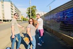 Tres amigos despreocupados que toman la 'promenade' en la ciudad Fotos de archivo libres de regalías