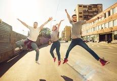 Tres amigos despreocupados que toman la 'promenade' en la ciudad Imagen de archivo libre de regalías