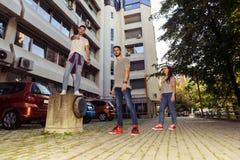 Tres amigos despreocupados que toman la 'promenade' en la ciudad Fotografía de archivo