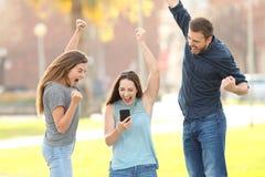 Tres amigos emocionados que saltan comprobando el tel?fono elegante en un parque imágenes de archivo libres de regalías