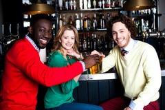 Tres amigos en barra que gozan de la cerveza Fotografía de archivo
