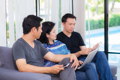 Tres amigos en línea con los dispositivos múltiples y sentarse que habla en un sofá Fotografía de archivo libre de regalías
