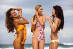Tres amigos en trajes de baño en la playa Imágenes de archivo libres de regalías