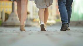 Tres amigos están caminando en el pavimento en el mediodía Se están divirtiendo en este tiempo soleado y del calor metrajes