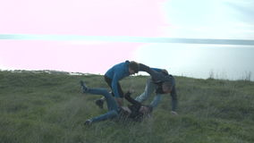 Tres amigos felices balancean alrededor en naturaleza que se abrazan