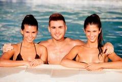 Tres amigos felices en la piscina Imagen de archivo libre de regalías
