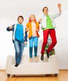 Tres amigos felices que saltan en el sofá blanco Imagen de archivo libre de regalías