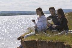 Tres amigos felices que se sientan en la colina que goza de la reconstrucción al aire libre y del té de las bebidas foto de archivo libre de regalías
