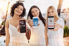 Tres amigos femeninos alegres que discuten la celebridad fotos de archivo libres de regalías