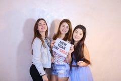 Tres amigos femeninos elegantes que presentan con la muestra y que piden sh Imagen de archivo