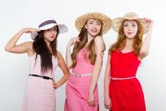 Tres amigos femeninos en el fondo blanco Foto de archivo libre de regalías