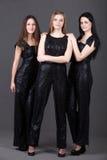 Tres amigos femeninos en traje de la tarde Imagenes de archivo