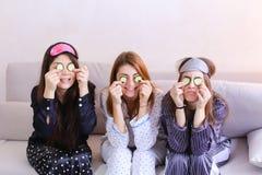 Tres amigos femeninos encantadores relajan y hacen la invitación facial de la belleza fotografía de archivo libre de regalías