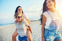 Tres amigos femeninos felices que caminan en la playa fotografía de archivo