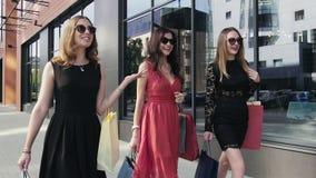 Tres amigos femeninos hermosos que caminan a lo largo de las ventanas de las compras Cámara lenta almacen de video