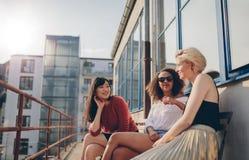 Tres amigos femeninos jovenes que se sientan en balcón imagenes de archivo