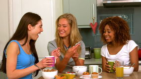 Tres amigos femeninos jovenes sonrientes que leen el mensaje de texto metrajes