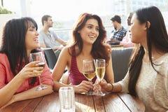 Tres amigos femeninos que disfrutan de la bebida en la barra al aire libre del tejado imagen de archivo libre de regalías