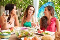 Tres amigos femeninos que disfrutan de la comida al aire libre en casa foto de archivo libre de regalías