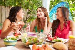 Tres amigos femeninos que disfrutan de la comida al aire libre en casa foto de archivo