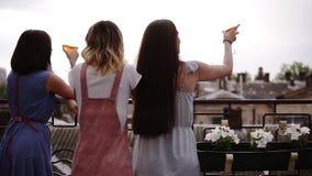 Tres amigos femeninos que disfrutan del partido de gallina en la terraza, opinión de la parte trasera Suposición, ropa moderna Op almacen de video