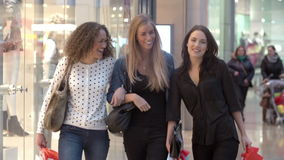 Tres amigos femeninos que hacen compras en alameda junto almacen de metraje de vídeo
