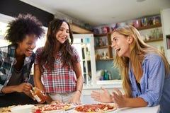 Tres amigos femeninos que hacen la pizza en cocina junta Foto de archivo