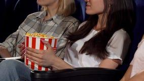 Tres amigos femeninos que miran películas en el cine metrajes