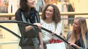 Tres amigos femeninos que montan compras de la escalera móvil en alameda almacen de metraje de vídeo
