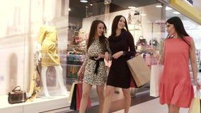 Tres amigos femeninos que salen de la tienda almacen de metraje de vídeo