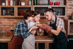 Tres amigos gozan del olor de la pizza recientemente cocida foto de archivo libre de regalías