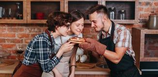 Tres amigos gozan del olor de la pizza recientemente cocida fotografía de archivo libre de regalías