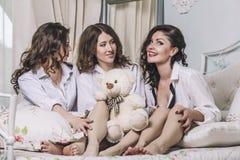 Tres amigos hermosos de las mujeres jovenes que charlan en el dormitorio adentro Fotos de archivo libres de regalías