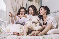 Tres amigos hermosos de las mujeres jovenes que charlan en el dormitorio adentro Foto de archivo